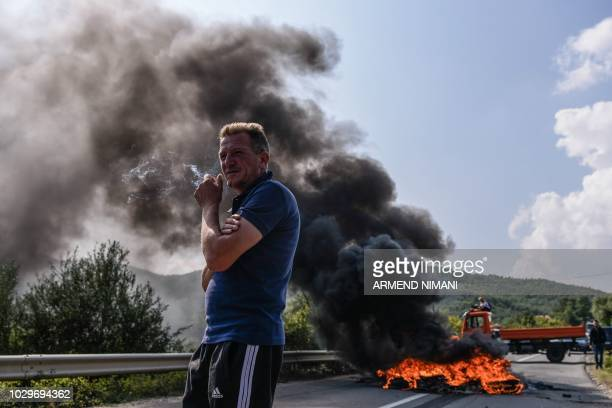 Kosovo Albanians smokes by a barricade and smoke billows from burning tires as hundreds block on September 9 2018 access to a village due to be...