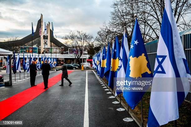 Kosovo Albanians walk past Israeli's and Kosovo's flag displayed during a ceremony at the headquarters of the Foreign Ministry in Pristina on...
