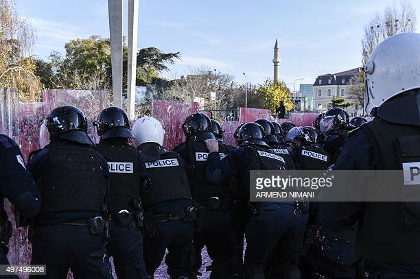 Kosovo antiriot police officers take cover during clashes with supporters of opposition parties near the Kosovo's parliament in Pristina on November...
