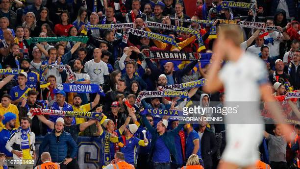 Kosovo fans wave flags as England's striker Harry Kane reacts after his penalty kick was saved during the UEFA Euro 2020 qualifying Group A football...