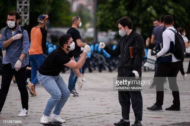 Kosovo muslim believers wearing protective face masks and gloves greet each other after praying at the Skanderbeg Square of Pristina on May 19 in a...