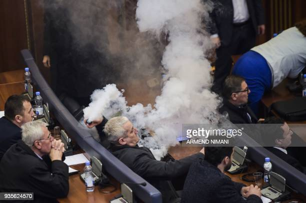 A Kosovo opposition lawmaker throws a tear gas canister during a parliament session in Pristina on March 21 2018 before a vote to ratify or not a...