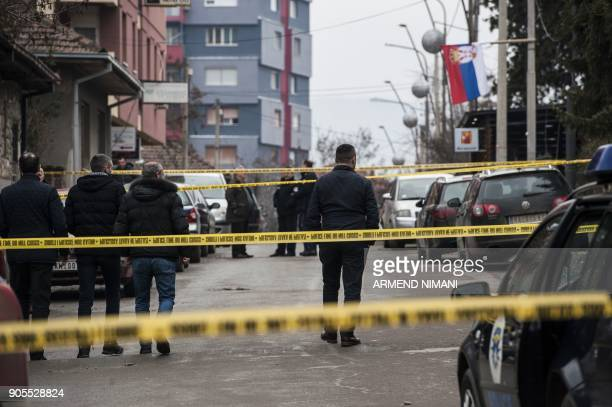 Kosovo police officers and forensics walk paste the crime scene where the leading Kosovo Serb politician Oliver Ivanovic was killed in a brazen...