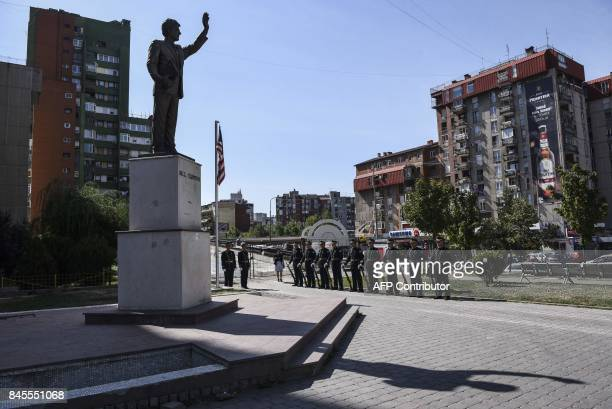 Kosovo Police officers ceremonial guard stand at ease next to the statue of former US President Bill Clinton in Pristina on September 11 2017 during...
