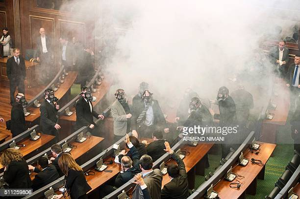 TOPSHOT Kosovo police officers weeraing gas masks inspect the parliament after tear gas was launched by opposition lawmakers disrupting the first...