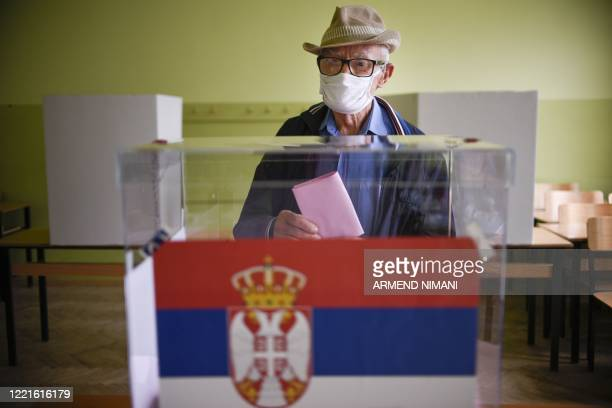 Kosovo Serb wears a facemask as he casts his vote at a polling station in Gracanica on June 21 during an election for a new parliament in Europe's...