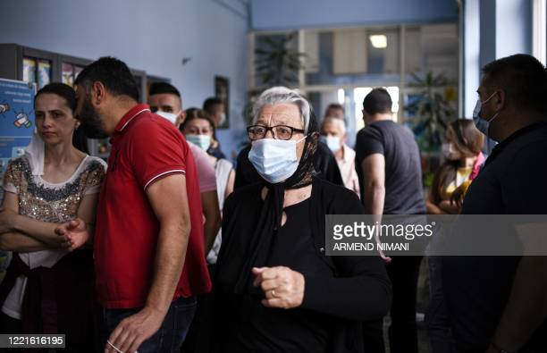 Kosovo Serb wears a facemask as she arrives to cast her vote at a polling station in Gracanica on June 21 during an election for a new parliament in...