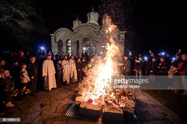 Kosovo Serbs throw oak branches into the bonfire outside the Medieval Monastery in the town of Gracanica during the ceremonial burning of dried oak...