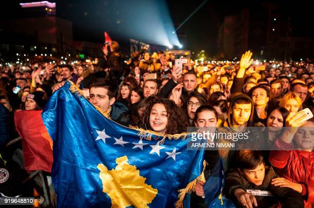 Kosovo's Albanians wave Kosovo flag during a concert by Pristinaborn British singer and actress Rita Ora in Pristina on February 17 2018 on the...
