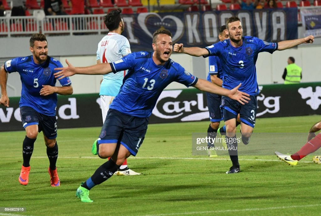 Kosovo's Amir Rrahmani (C) celebrates with teammates Enis Alushi (L) and Fidan Aliti (R) after scoring during the FIFA World Cup 2018 qualification football match between Kosovo and Turkey at Loro Borici stadium in Shkoder on June 11, 2017. / AFP PHOTO / Gent SHKULLAKU