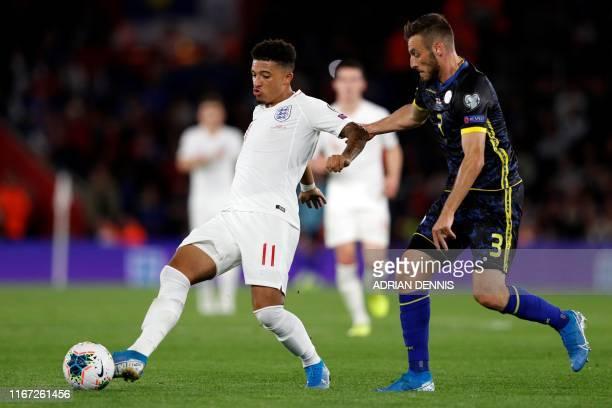 Kosovo's defender Fidan Aliti vies with England's midfielder Jadon Sancho during the UEFA Euro 2020 qualifying Group A football match between England...
