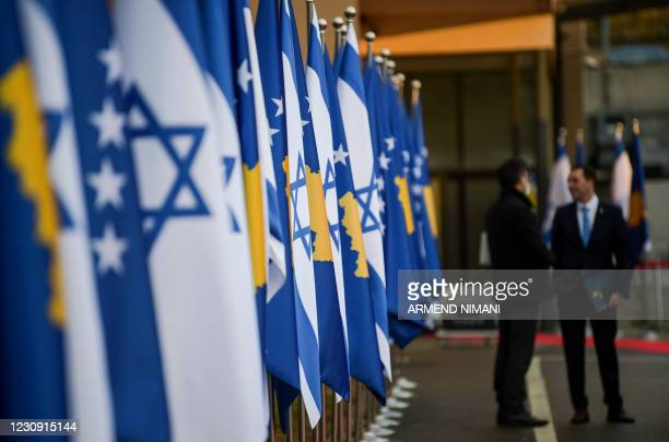 Kosovo's government officials stand in front of Kosovo's and Israel's flags displayed during a ceremony at the headquarters of the Foreign Ministry...