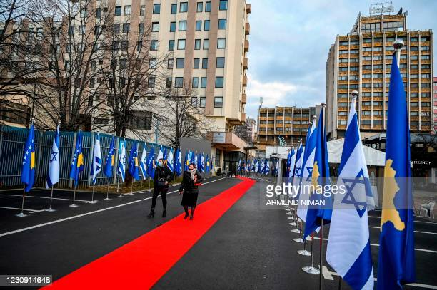 Kosovo's government officials walk past Israeli's and Kosovo's flag displayed during a ceremony at the headquarters of the Foreign Ministry in...