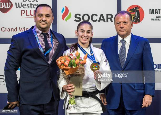 Kosovo's judo coach Driton Kuka proudly stands alongside Kosovo's u57kg gold medalist together with the International Judo Federation's President...