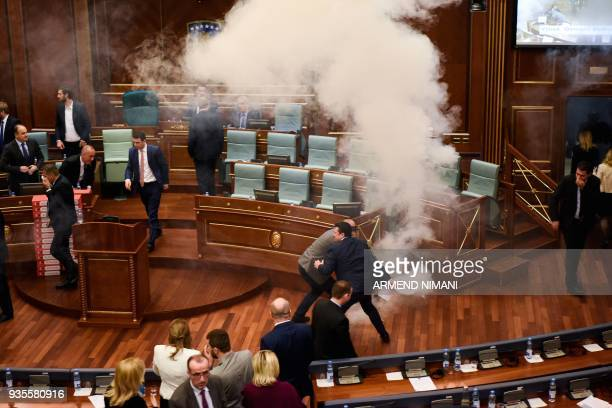 Kosovo's lawmakers react after opposition members released a teargas canister inside the country's parliament in Pristina on March 21 2018 before a...