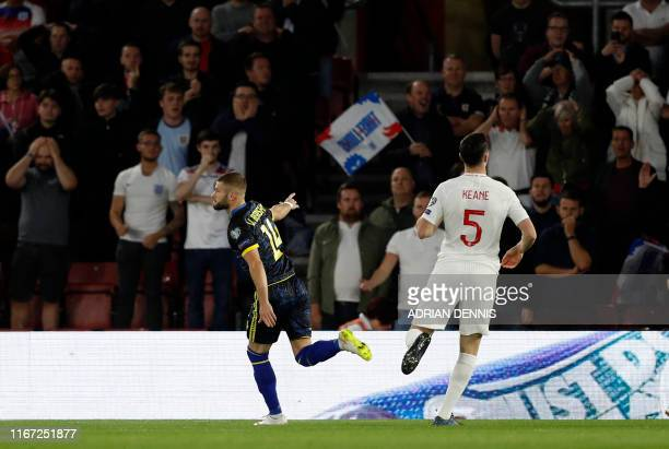 Kosovo's midfielder Valon Berisha passes England's defender Michael Keane as he celebrates scoring the opening goal during the UEFA Euro 2020...