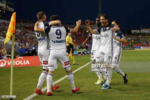 Kosta Barbarouses celebrates his goal with Besart Berisha and Mark Milligan of the Victory during the round eight ALeague match between the Newcastle...
