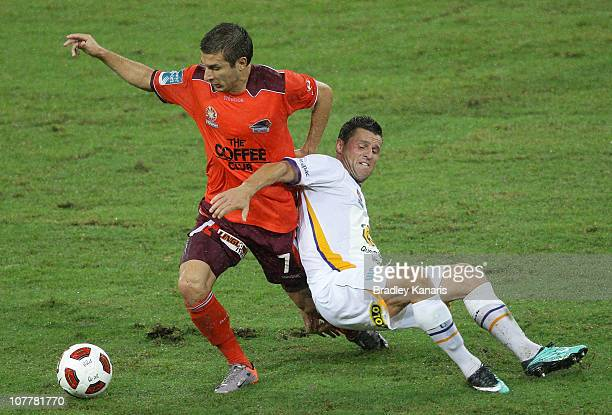 Kosta Barbarouses of the Roar is challenged by Jason Culina of the Gold Coast during the round 20 ALeague match between the Brisbane Roar and Gold...