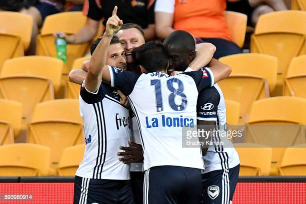 Kosta Barbarouses of the Victory celebrates with team mates after scoring a goal during the round 11 ALeague match between the Brisbane Roar and the...