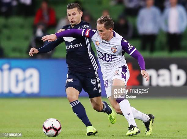 Kosta Barbarouses of the Victory competes for the ball against Neil Kilkenny of the Glory during the round two ALeague match between the Melbourne...