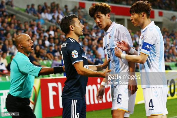 Kosta Barbarouses of the Victory is confrontedd by Jeong Jae Yong and Kang MinSoo of Ulsan Hyundai after tackling Park Joo Ho of Ulsan Hyundai during...