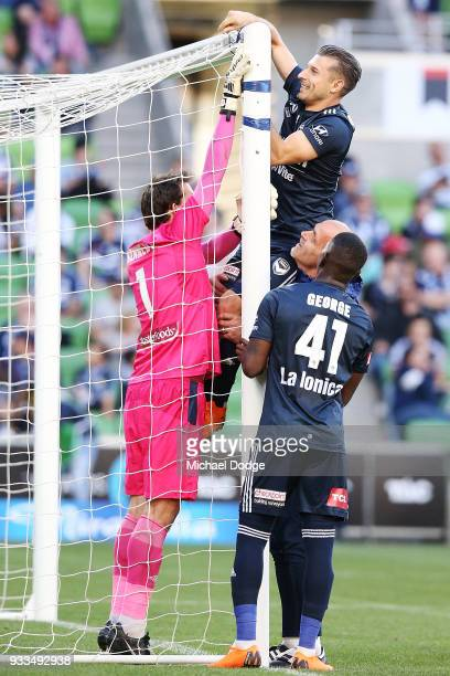 Kosta Barbarouses of the Victory is hoisted up to fix the broken net by Victory goalkeeper coach Dean Anastasiadis Leroy George of the Victory and...