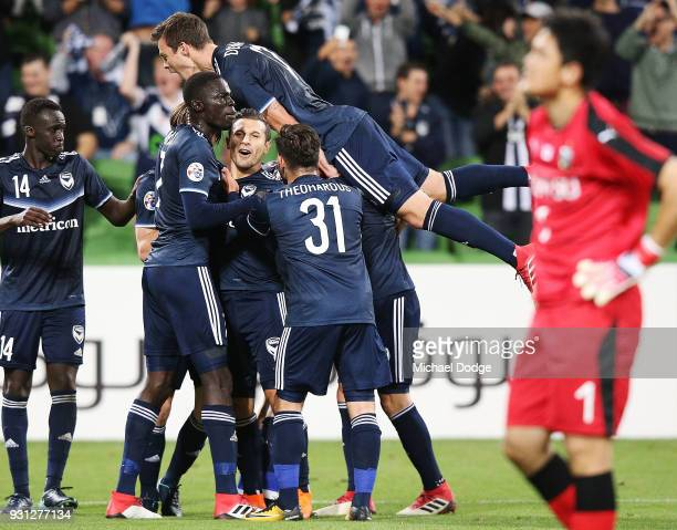 Kosta Barbarouses of the Victory is mobbed after scoring a goal in the dying stages during the AFC Asian Champions League match between the Melbourne...