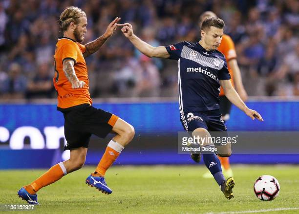 Kosta Barbarouses of the Victory kicks the ball at goal from Jacob Pepper of Brisbane Roar during the A-League Rd 22 match between Melbourne Victory...