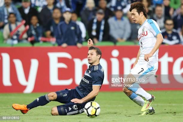 Kosta Barbarouses of the Victory passes the ball past Shintaro Kurumaya of Kawasaki Frontale during the AFC Asian Champions League match between the...