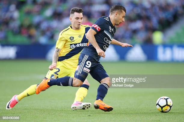 Kosta Barbarouses of the Victory runs with the ball past Storm Roux of the Mariners during the round 23 ALeague match between the Melbourne Victory...