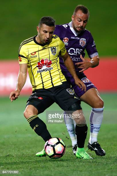 Kosta Barbarouses of Wellington is put under pressure from Marc Warren of Perth during the round 22 ALeague match between the Wellington Phoenix and...