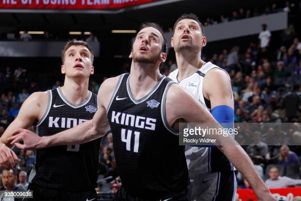 Kosta Koufos and Bogdan Bogdanovic of the Sacramento Kings box out Nikola Vucevic of the Orlando Magic on March 9 2018 at Golden 1 Center in...