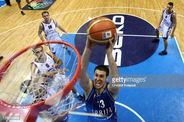 Kosta Perovic of Serbia dunks the ball against Martins Meiers and Rolands Freimanis of Latvia during the EuroBasket 2011 first round group B match...