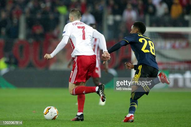 Kostas Fortounis of Olympiacos FC attacking and Joe Willock of Arsenal FC during the UEFA Europa League round of 32 first leg match between...