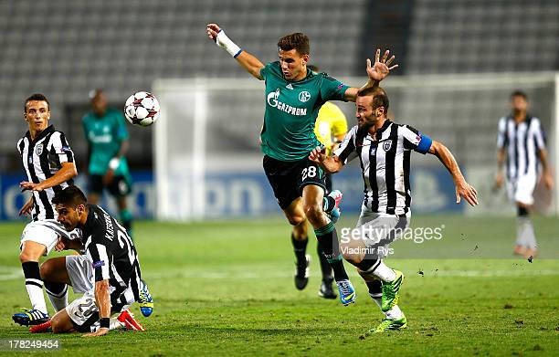 Kostas Katsouranis and Dimitris Salpingidis of PAOK defend Adam Szalai of Schalke during the UEFA Champions League second leg playoff match between...