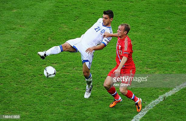 Kostas Katsouranis of Greece and Denis Glushakov of Russia battle for the ball during the UEFA EURO 2012 group A match between Greece and Russia at...