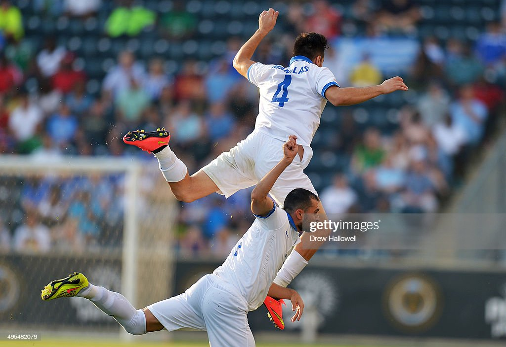 Kostas Manolas #4 of Greece leaps over teammate Loukas Vyntra #11 while going for the ball against Nigeria during an international friendly match at PPL Park on June 3, 2014 in Chester, Pennsylvania.