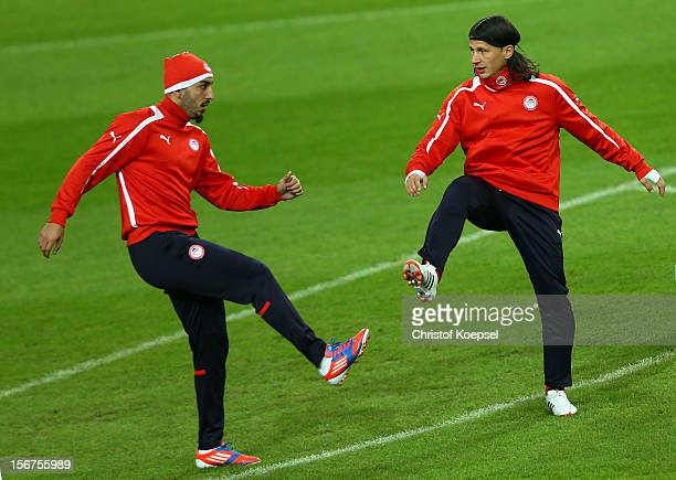 Kostas Mitroglou and Marko Pantelic of Olympiacos Piraeus stretch during the training session at Veltins Arena ahead of the UEFA Champions League...