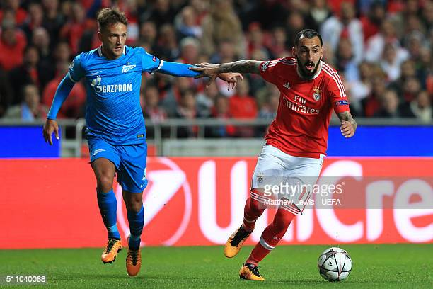 Kostas Mitroglou of Benfica holds off Domenico Criscito of FC Zenit during the first leg of the UEFA Champions League Round of 16 match between SL...