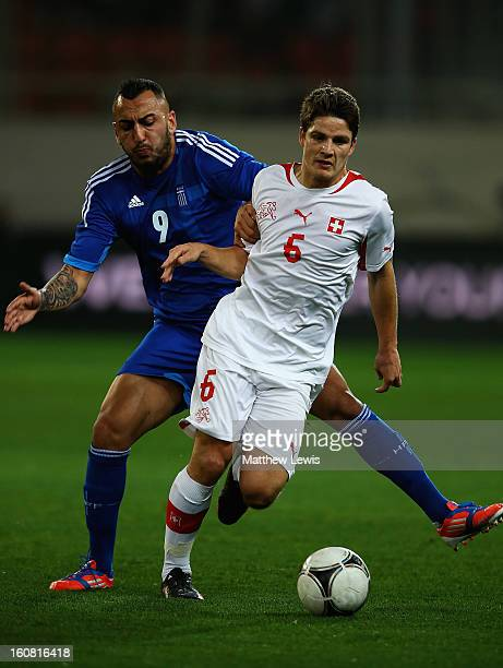 Kostas Mitroglou of Greece and Pirmin Schwegler of Switzerland challenge for the ball during the International Friendly match between Greece and...