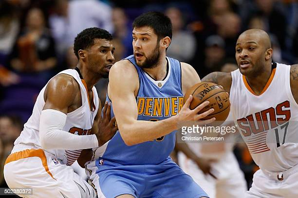 Kostas Papanikolaou of the Denver Nuggets looks to pass under pressure from Ronnie Price and PJ Tucker of the Phoenix Suns during the second half of...
