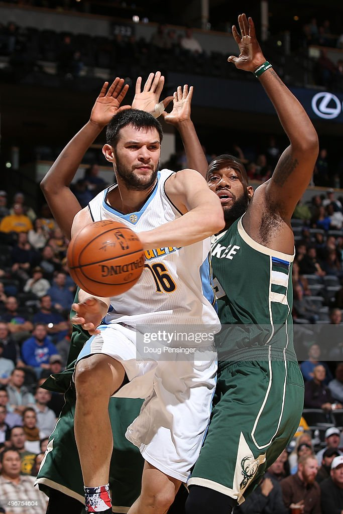 Kostas Papanikolaou #16 of the Denver Nuggets passes the ball against the defense of Greg Monroe #15 of the Milwaukee Bucks at Pepsi Center on November 11, 2015 in Denver, Colorado. The Nuggets defeated the Bucks 103-102.