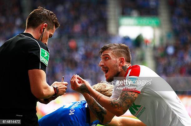 Kostas Stafylidis of Augsburg argues with the referee after injuring Breel Donald Embolo of Schalke 04 during the Bundesliga match between FC...