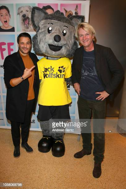 Kostja Ullmann and Detlev Buck pose with mascot Jacky at the movie premiere of 'Wuff' at Mathaeser Filmpalast on October 22 2018 in Munich Germany