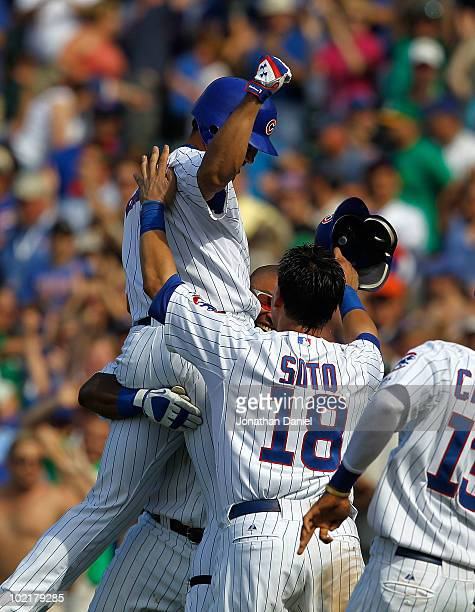 Kosuke Fukudome of the Chicago Cubs celebrates his gamewinning hit in the bottom of the 9th inning against the Oakland Athletics with teammates...