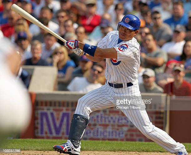 Kosuke Fukudome of the Chicago Cubs hits a sacrifice fly to drive in Jeff Baker in the seventh inning of a MLB against the Milwaukee Brewers at...