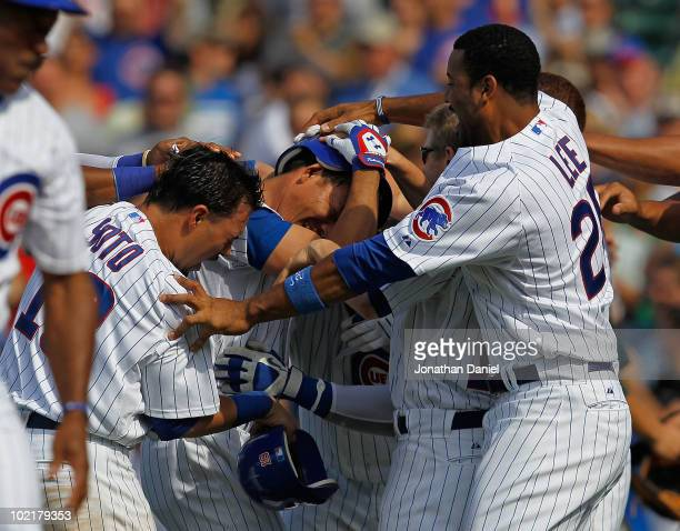Kosuke Fukudome of the Chicago Cubs is mobbed by teammates including Geovany Soto and Derrick Lee after getting the gamewinning hit in the bottom of...