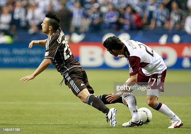 Kosuke Kimura of the Colorado Rapids trips up Davide Chiumiento of the Vancouver Whitecaps FC during their MLS game June 16 2012 in Vancouver British...