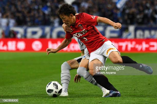 Kosuke Onose of Gamba Osaka and Tomoya Ugajin of Urawa Red Diamonds compete for the ball during the J.League J1 match between Urawa Red Diamonds and...