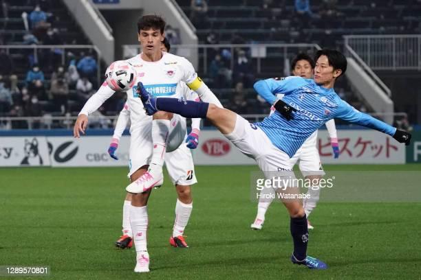 Kosuke Saito of Yokohama FC and Eduardo of Sagan Tosu compete for the ball during the J.League Meiji Yasuda J1 match between Yokohama FC and Sagan...